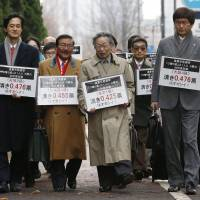 Seeking balance: Lawyers led by Hidetoshi Masunaga (center) hold signs pointing out the disparity in vote values between the most- and least-populated districts as they walk to the Tokyo High Court on Monday.   KYODO