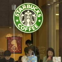 Taking a break: Three women drink coffee at one of Starbucks' coffee shops in Tokyo. | BLOOMBERG