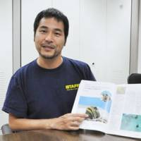 Rare creature: Kentaro Amemiya explains his work with jawfish at Tokyo Sea Life Park in September using a magazine article about the mouthbreeding fish. | KYODO