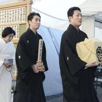 Final respects: Nakamura Kanzaburo's sons — Kankuro (right) and Shichinosuke — walk in front of Kanzaburo's wife, Yoshie, at the late kabuki master's funeral at Tokyo's Tsukiji Honganji Temple on Thursday. | KYODO
