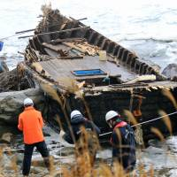 Lost: Police officers check an open wooden boat that washed ashore on Sado Island, Niigata Prefecture, on Nov. 29 and is believed to have originated in North Korea.   KYODO
