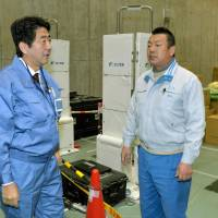 In your debt: Prime Minister Shinzo Abe (left) voices his gratitude to a worker at J Village in Fukushima Prefecture before visiting the Fukushima No. 1 nuclear plant Saturday.   KYODO