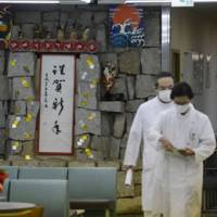 No allergy: Doctors walk through a hallway decorated with New Year's greetings Friday night at Yokohama Denentoshi Hospital, where four patients died of norovirus infections. | KYODO