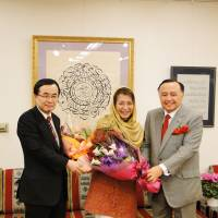 Saudi Arabian Ambassador Abdulaziz Turkistani (right), with Kazuyuki Hamada, then parliamentary vice minister for foreign affairs, congratulates Nobuko Sagawa (center), a Japanese specialist in Arabic calligraphy, at his embassy in Tokyo on Dec. 20. | EMBASSY OF SAUDI ARABIA