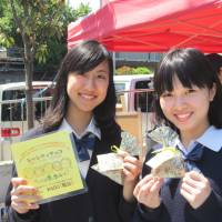 Sweet charity: Mayuko Sako and Saki Nishino of Free The Children Japan sell chocolates at a Tokyo street performance festival in Suginami Ward on Sunday. A portion of the proceeds will be used to help build a school in India.   COURTESY OF FREE THE CHILDREN JAPAN