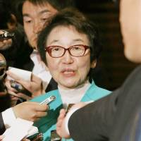 Under fire: Yoriko Kawaguchi, chairwoman of the Upper House Environment Committee, is surrounded by reporters after a meeting with Prime Minister Shinzo Abe in Tokyo on Tuesday night. | NIHON KEIZAI SHIMBUN/KYODO