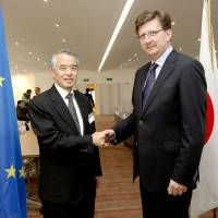 Start: Japan's chief negotiator, Jun Yokota (left), shakes hands with his European Union counterpart, Mauro Petriccione, as they launch the first round of free trade agreement negotiations between the EU and Japan, in Brussels on April 15. | EUROPEAN UNION