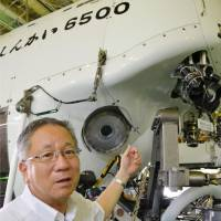 Grand tour: Hiroshi Kitazato of the Japan Agency for Marine-Earth Science and Technology points at the Shinkai 6500 manned submersible Sunday in Rio de Janeiro. | KYODO