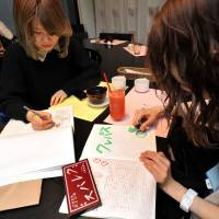 Practice makes perfect: Customers at bunbougu cafe in Tokyo's fashionable Omotesando district April 19 have free use of pencils and notebooks while they dine. | YOSHIAKI MIURA