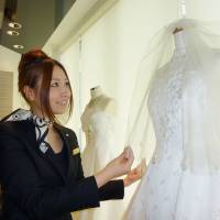 Within reach: An official at Mation Inc., which offers wedding services at a low cost, looks at a wedding dress at its showroom in Tokyo's Shinjuku Ward last month. | KYODO