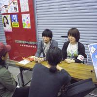 Sympathetic ears: Shinichi Tokita (left) and Lim Moon Hyang listen to passersby talk about their problems on a shopping street in Tokyo's Koenji area. | TOMOHIRO OSAKI