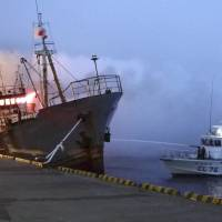 Gutted: A Japan Coast Guard vessel uses its water cannon as flames pour from the bridge of the 497-ton Cambodia-registered freighter Taigan early Thursday in Wakkanai port in Hokkaido. | JAPAN COAST GUARD/KYODO