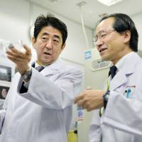 Traveling man: Prime Minister Shinzo Abe listens to explanations about state-of-the-art medical technologies at Kyushu University Hospital in Fukuoka on Sunday. | KYODO