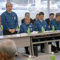 Up to his neck: Tokyo Electric Power Co. Managing Executive Officer Tsunemasa Niitsuma discusses the water crisis at the Fukushima No. 1 nuclear plant with fishermen in Iwaki, Fukushima Prefecture, on April 24. The radioactive water at the crippled plant, shown in March, can't be stopped unless the reactor leaks are plugged and may soon exhaust all storage. | KYODO