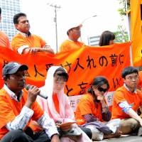 Staying put: Foreigners without proper visas, along with families and supporters, continue a sit-in outside the Tokyo Regional Immigration Bureau in Minato Ward on Tuesday. They plan a five-day protest. | SATOKO KAWASAKI