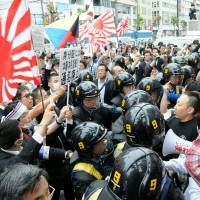 Provocateurs: Riot police prevent an anti-Korean group (at left) and Korean residents and their supporters from clashing Sunday in the Shin-Okubo district in Tokyo. | SATOKO KAWASAKI