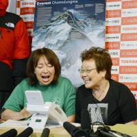 Family pride: Yuichiro Miura's daughter, Emiri, and wife, Tomoko, speak with the alpinist from Tokyo on Thursday after he reached the top of Mount Everest. | KYODO