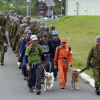 Search on: Self-Defense Force personnel and others leave Tuesday morning to search for two elementary school children from Osaka who were reported missing Monday on a mountain in Shiga Prefecture. The two later found their way to safety. | KYODO