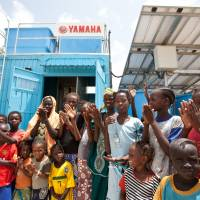 Turning on the tap: Senegalese villagers gather around a water treatment plant in Ndiawdoune Nar last August. | JICA/SHINICHI KUNO/YAMAHA MOTOR CO.