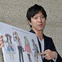 Giving life: Meru Kishida shows off his illustrations of characters representing the World Cosplay Summit during a recent visit to the Chunichi Shimbun's offices in Nagoya. | CHUNICHI SHIMBUN