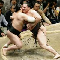 Perfect example: Hakuho (right) tussles with Harumafuji on his way to victory with a flawless record at the Summer Grand Sumo Tournament on Sunday. | KYODO
