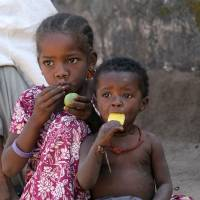 African roots: Sidi children, descendants of ninth-century African migrants, eat fruit outside their home in Jambur, in western India. 