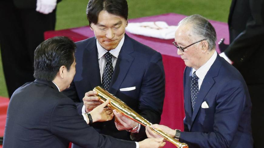 Special recognition: Prime Minister Shinzo Abe presents Hideki Matsui (center) and Shigeo Nagashima (right) a commemorative gold bat as part of their People's Honor Award ceremony on Sunday before the Yomiuri Giants-Hiroshima Carp game at Tokyo Dome. | KYODO