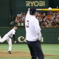One pitch for Godzilla: Former Yomiuri Giants and MLB star Hideki Matsui tosses the ceremonial first pitch as Shigeo Nagashima stands in the batter's box on Sunday. | KYODO