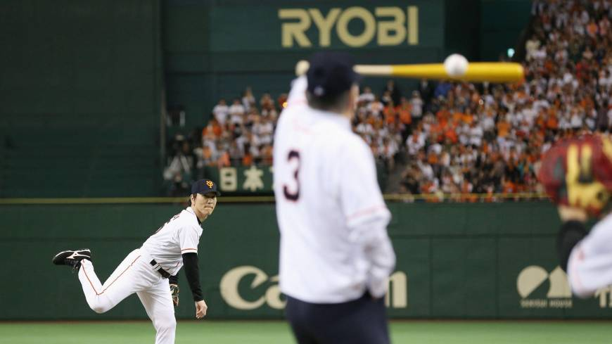 One pitch for Godzilla: Former Yomiuri Giants and MLB star Hideki Matsui tosses the ceremonial first pitch as Shigeo Nagashima stands in the batter's box on Sunday.