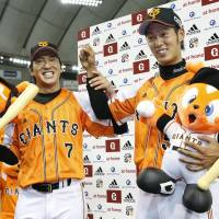 Orange crush: Hisayoshi Chono (left) and Soichiro Tateoka celebrate after the Giants' 5-4 win over the Marines on Wednesday. | KYODO