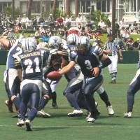 Long arm of the law: Quarterback Gaku Matsuoka (3) of the Metropolitan Police Department Eagles hands the ball off to running back Kokichiro Nagatani during Monday's game against the Tokyo Gas Creators. | KAZ NAGATSUKA