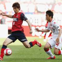 Finishing touch: Kashima Antlers striker Yuya Osako (left) scores his side's third goal in a 3-1 win over Nagoya Grampus on Saturday. | KYODO