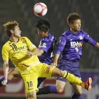 Better than nothing: Kashiwa's Junya Tanaka vies for the ball against two Hiroshima players on Wednesday night.   KYODO