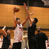 Chosen one: Yuta Watanabe attempts to block a shot from veteran player Kosuke Takeuchi during an intra-squad game at the Japan men's national team training camp in Tokyo last Friday. | KAZ NAGATSUKA