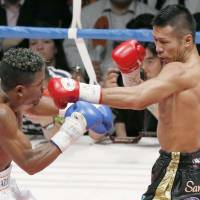 WBA super featherweight champion Takashi Uchiyama connects with a punch at Venezuelan challenger Jaider Parra. | KYODO