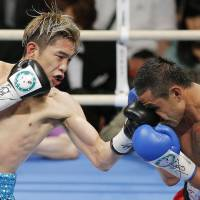 Take that: Kazuto Ioka lands a punch during his bout against Wisanu Kokietgym on Wednesday in Osaka. Ioka won via knockout to retain his WBA light flyweight title. | KYODO