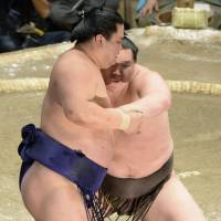 Step away: Hakuho (right) forces Myogiryu out of the raised ring on Tuesday at the Summer Grand Sumo Tournament in Tokyo. | KYODO