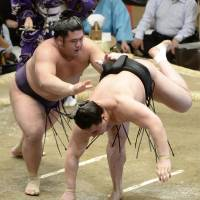 Down he goes: Tochiozan (left) sends Harumafuji to defeat on Thursday at the Summer Grand Sumo Tournament in Tokyo. | KYODO