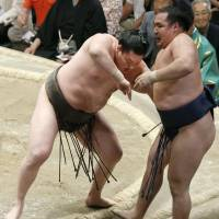 Show of force: Yokozuna Hakuho shoves ozeki Kakuryu out of the raised ring on Thursday at the Summer Grand Sumo Tournament. | KYODO