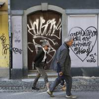 Bailout candidate: Pedestrians pass graffiti on a doorway between stores in Slovenia's capital of Ljubljana on Thursday. | BLOOMBERG