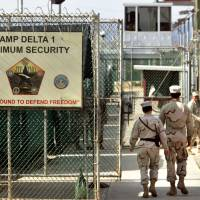 Indefinite detention: Military guards are seen walking at Camp Delta military prison at the U.S. naval base in Guantanamo Bay, Cuba, in 2006.   AP
