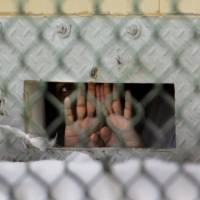 A detainee shields his face as he peers through the cell door opening used to pass food and other items to detainees. U.S. President Barack Obama has renewed his call to shut the facility. | AP
