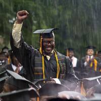 Recognition: Graduating student Frederick Anderson stands in the pouring rain as President Barack Obama acknowledges him during the Morehouse College 129th commencement ceremony on Sunday in Atlanta. | AP