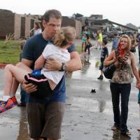 Blown away: Teachers carry children away from Briarwood Elementary School after a tornado ripped through the premises in Oklahoma City on Monday. | AP