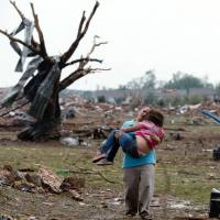 Twisted scene: A woman carries a child through a field near the collapsed Plaza Towers Elementary School in Moore, Oklahoma, on Monday. | AP