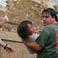 Weathering the storm: A child is carried from the rubble of the Plaza Towers Elementary School following a tornado in Moore, Oklahoma, on Monday. | AP
