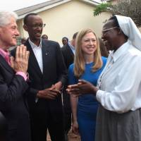 Old friends: Former U.S. President Bill Clinton greets a Rwandan school headmistress on July 19, 2012, as his daughter Chelsea Clinton and Paul Kagame look on. Bill Clinton once described Kagame as 'one of the greatest leaders of our time.'   AP