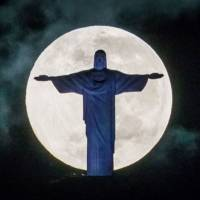 Lunar light show: The moon sets behind the Christ the Redeemer statue in Rio de Janeiro on Saturday. | AFP-JIJI