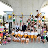 Children gather for a group photo at Byobugaura Harukaze, one of 69 nurseries that opened this spring as part of Yokohama's measures toward reducing the number of children on day-care waiting lists to zero. | YOSHIAKI MIURA
