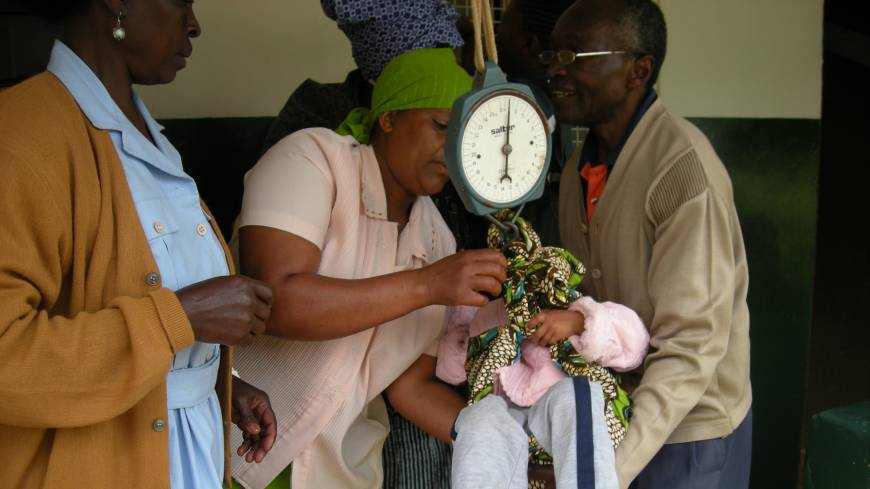 A nurse weighs a baby at a clinic in Moshi, Tanzania, in July 2010.